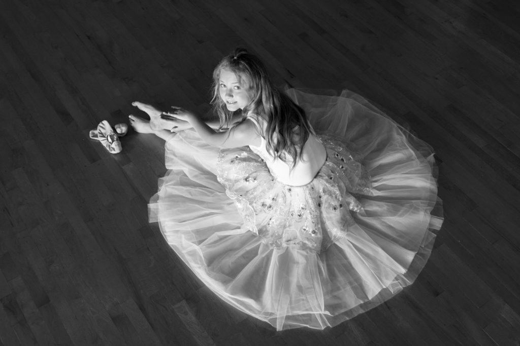 Black and white picture of a ballerina in a white tutu posing on a dance floor.