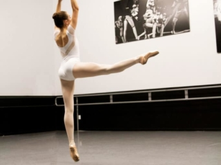 Ballerina in pointe shoes doing a jump.