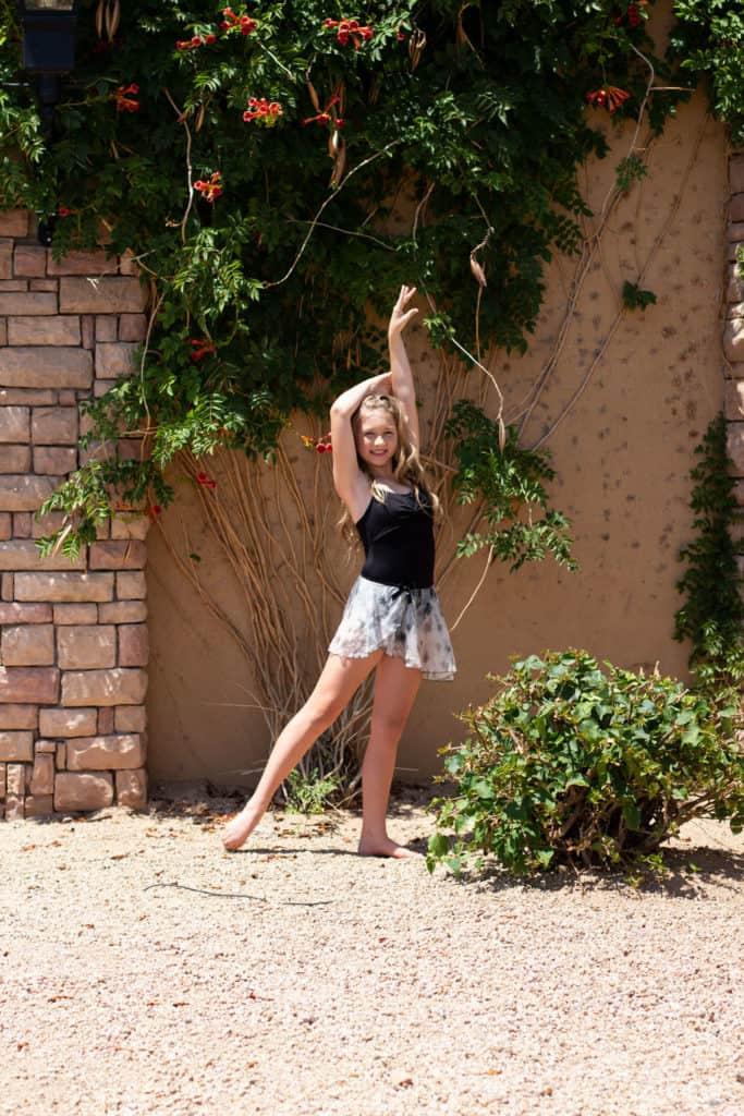 Dancer in a black leotard and dance skirt doing a dance pose in a garden.
