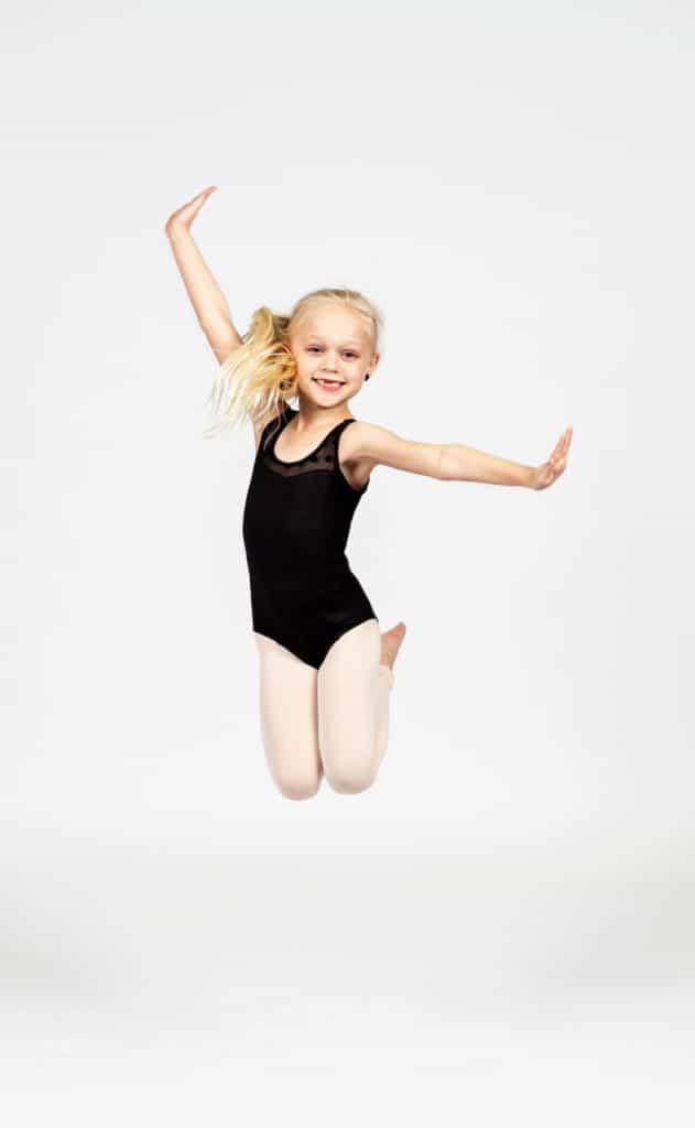 Dancer in a black leotard doing a dance jump.