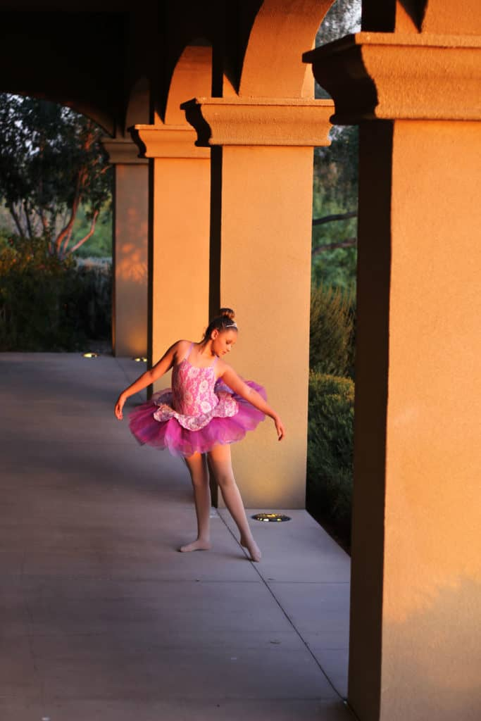 Ballerina in a pink tutu dancing in a fairytale forest between columns.