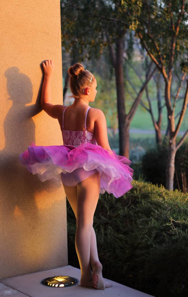 Ballerina in a pink tutu looking out into a fairytale forest.