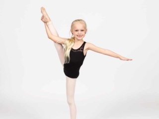 Dancer in black leotard doing a dance leg hold.
