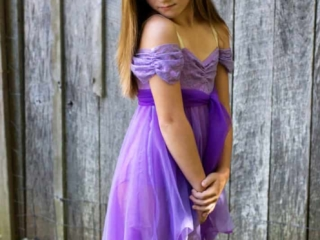 Lyrical dancer in a purple dress in a dance pose.