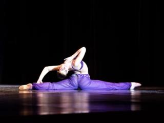 Arabian dancer in The Nutcracker doing the splits bending all the way back to head touching back leg.