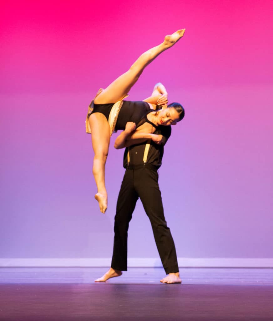 Dancer on stage doing an ariel while dance partner helps guide.