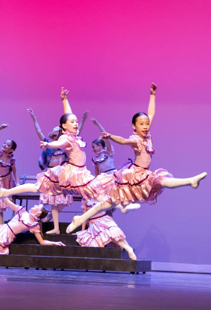 Ballet dancers doing a front leap on stage.