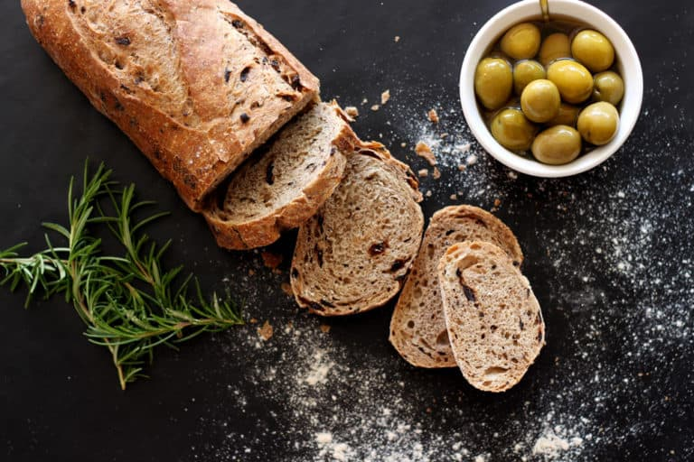 Loaf of olive bread sliced on a table, rosemary and green olives on table.