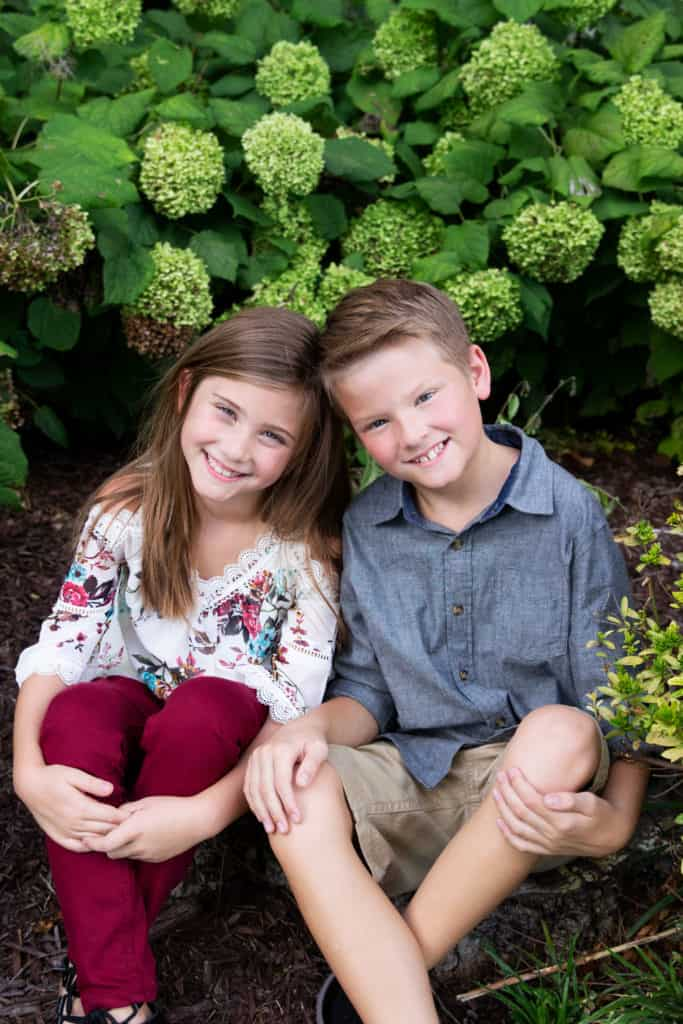 Brother and sister sitting in a garden, green flowers in background.