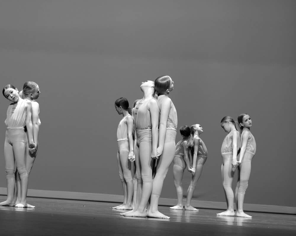 Black and white contemporary dance photo with dancers holding hands in an onstage performance.