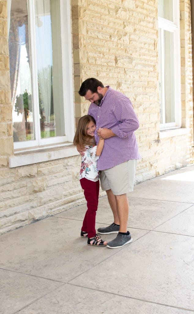 Daddy dancing with his daughter on a front porch of a southern plantation.