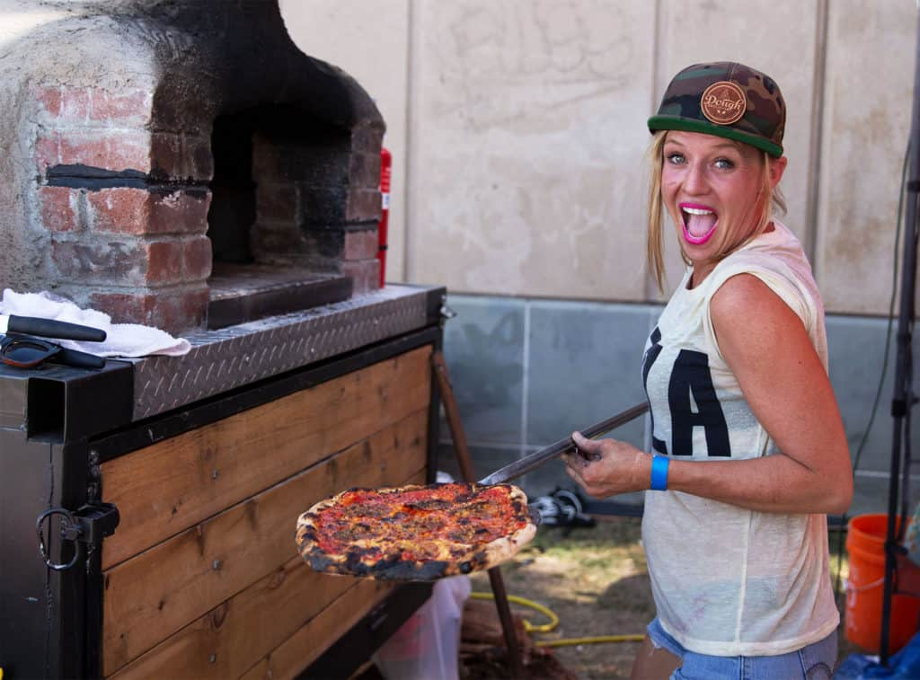 Lady placing a homemade pizza from Dough Broughs Pizza into a red brick oven at a food event in Scottsdale, Arizona.
