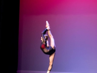 Solo lyrical dancer doing an extended scorpion on the dance stage for competition.