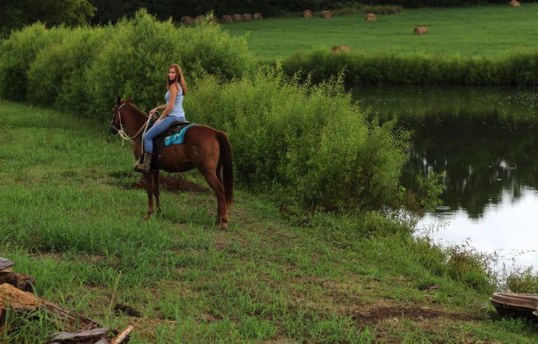Woman on a horse on a farm next to a farm.