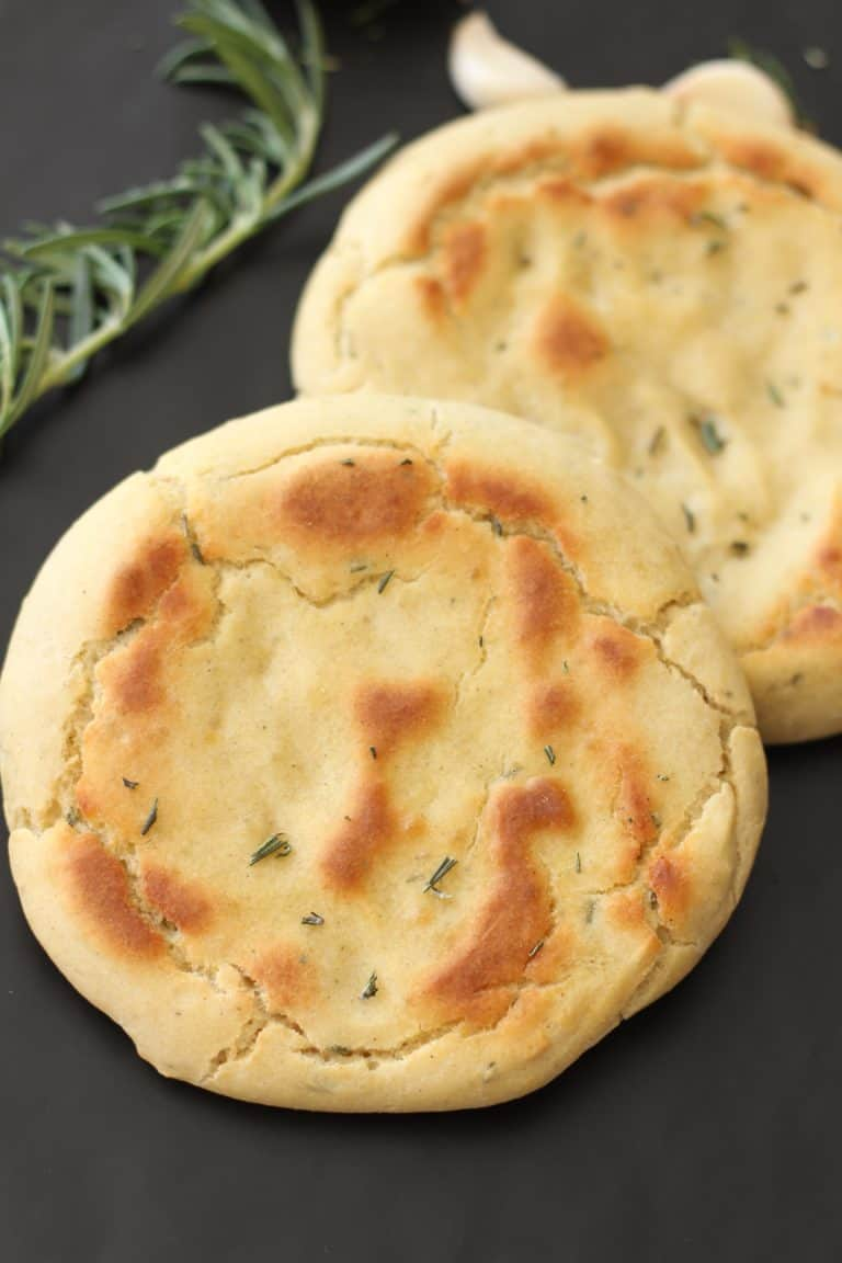 Two pieces of Rosemary Garlic Flatbread on a table with rosemary and garlic cloves.