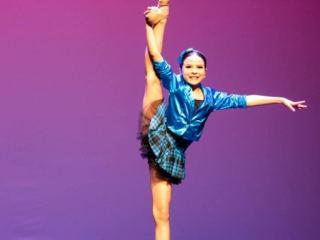 Jazz dancer in a dance pose holding a side leg hold.