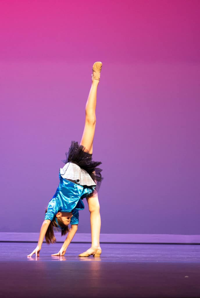 Jazz solo dancer doing a needle on stage for a dance competition performance.