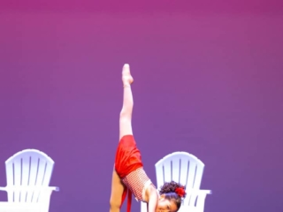 Solo dancer on stage during a dance competition doing a needle.