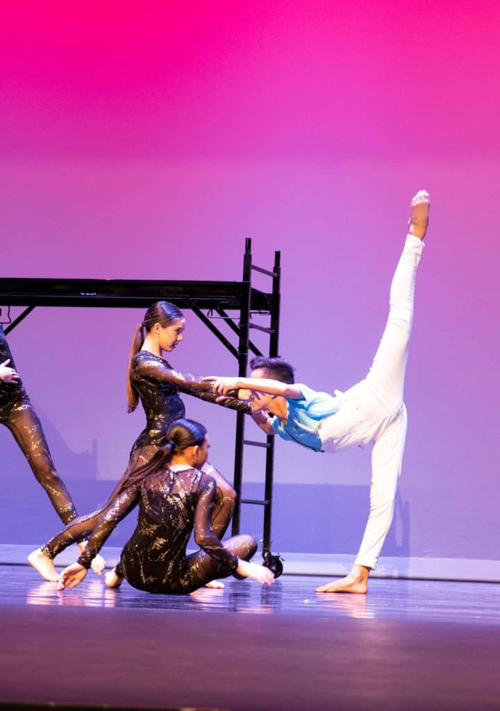 Jazz dancer on stage performing while doing a needle hold.