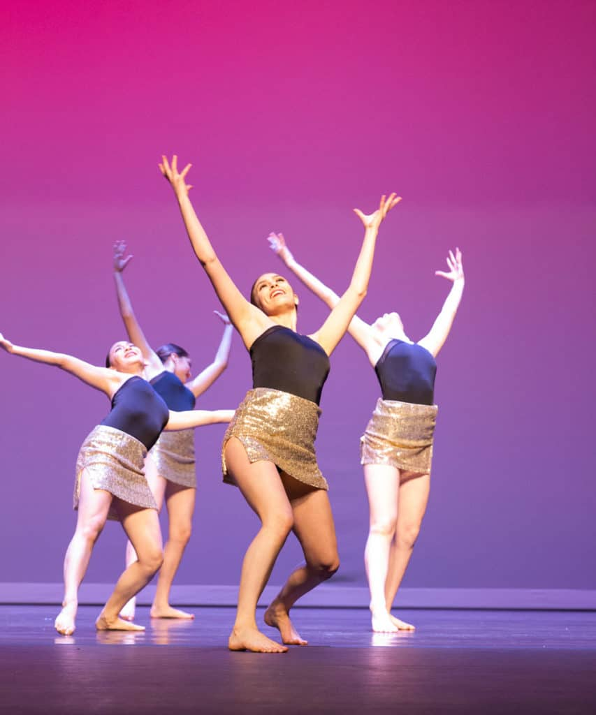 Jazz dancers performing on stage while throwing up their hands.