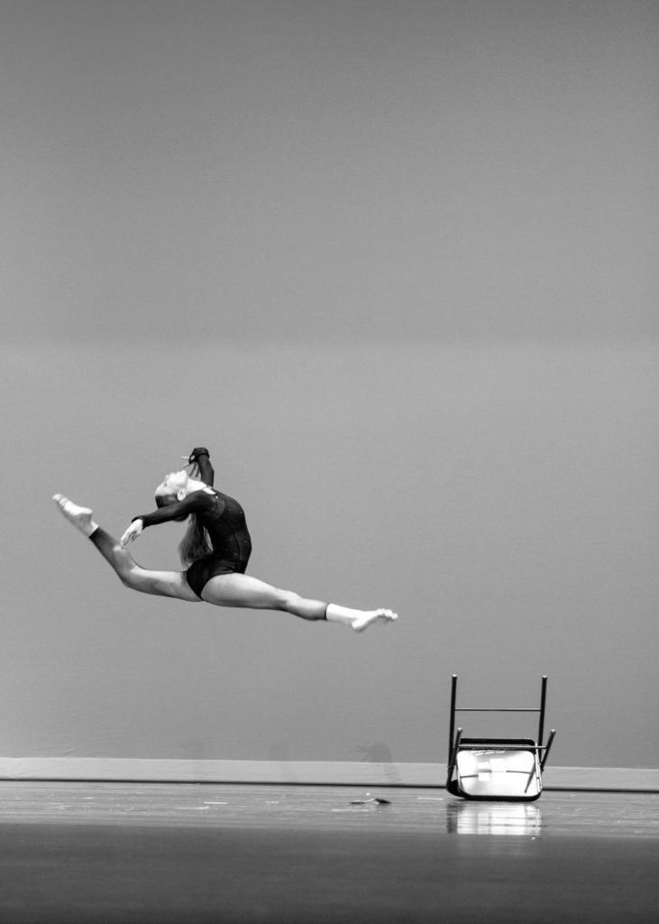 Black and white picture of a lyrical solo dancer on stage during dance competition.