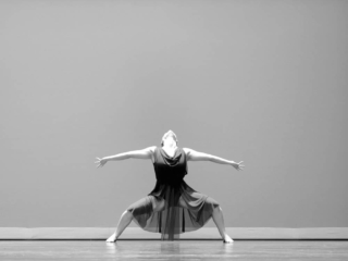 Black and white picture of a lyrical dancer leaning back with arms outstretched.