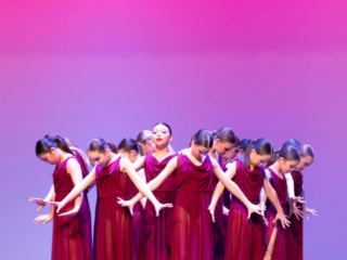 Group of lyrical dancers on stage performing at dance competition.