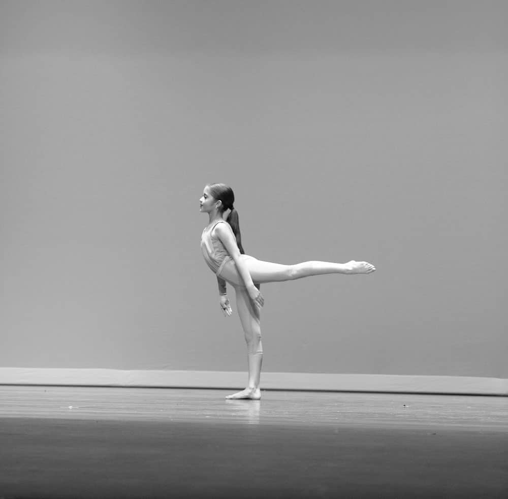 Black and white picture of a lyrical solo dancer on stage, leg hold back.