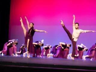 Lyrical dance performance with 2 soloists doing a side leg kick.