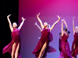 Lyrical dance group performing on stage in maroon dresses in a dance competition.