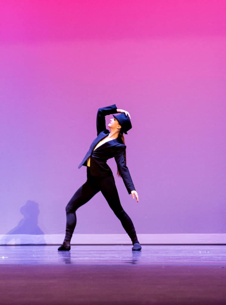 Picture of a dancer on stage touching a hat in a lyrical solo dance.