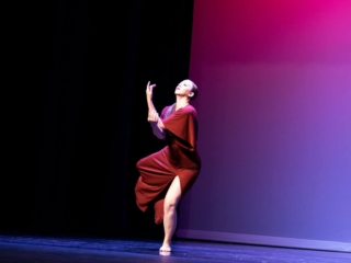 Lyrical dancer on stage in a red dress competing in a solo performance.