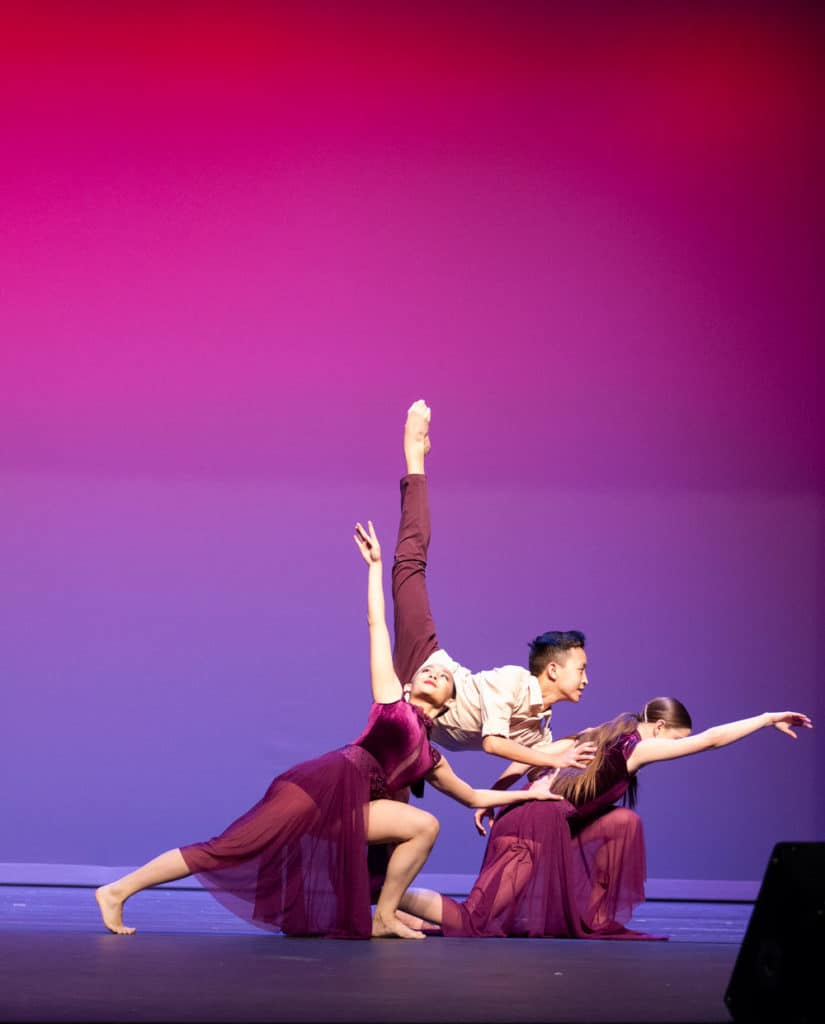 Three lyrical dancers on stage competing in a dance performance.