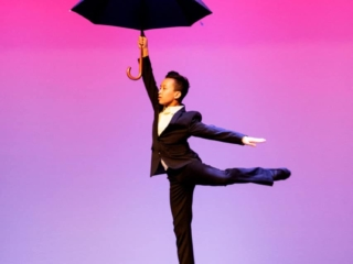 Solo dancer doing a back kick while holding a black umbrella while onstage.