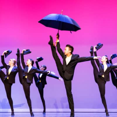 Musical theatre dance team performing on stage doing a leg kick, dancer holding an umbrella.