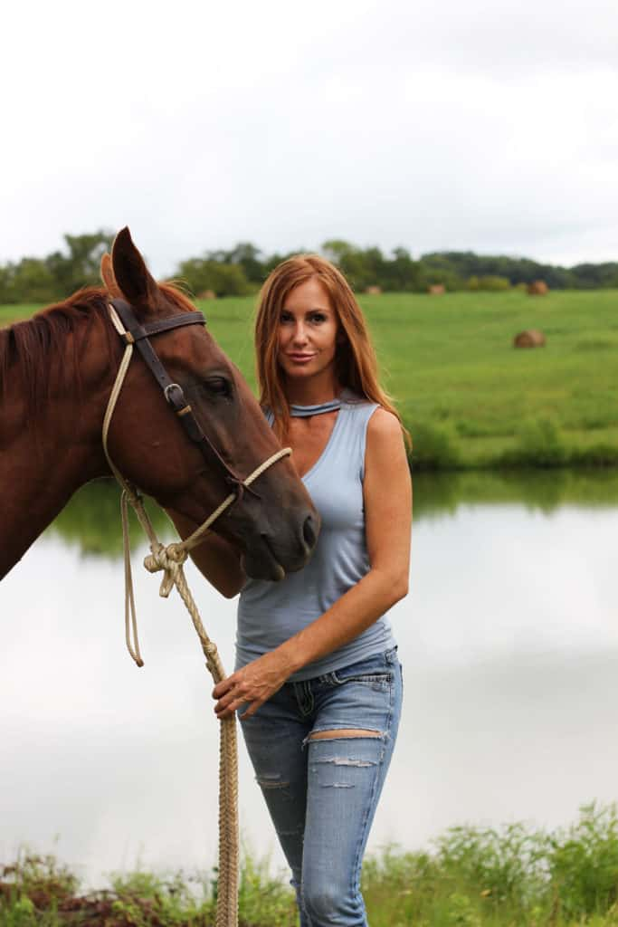 Girl holding a horse by the reins by a pond on a farm in Tennessee.