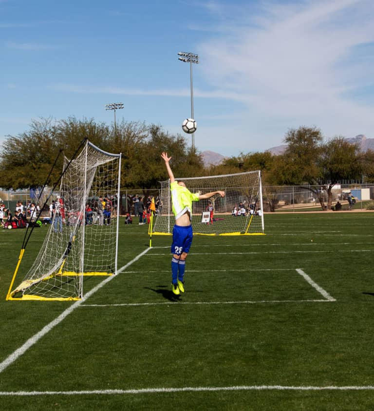 Soccer goalie blocking a soccer ball from going into the goal in a soccer game.