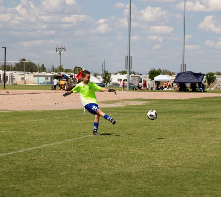 Soccer player kicking a soccer ball out of the goal in a soccer tournament.