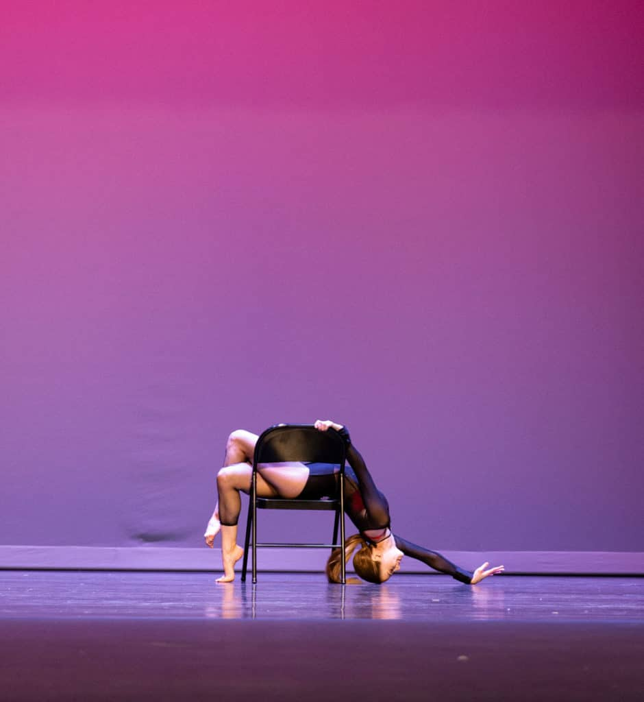 Solo lyrical dancer doing a backbend pose over a chair onstage.