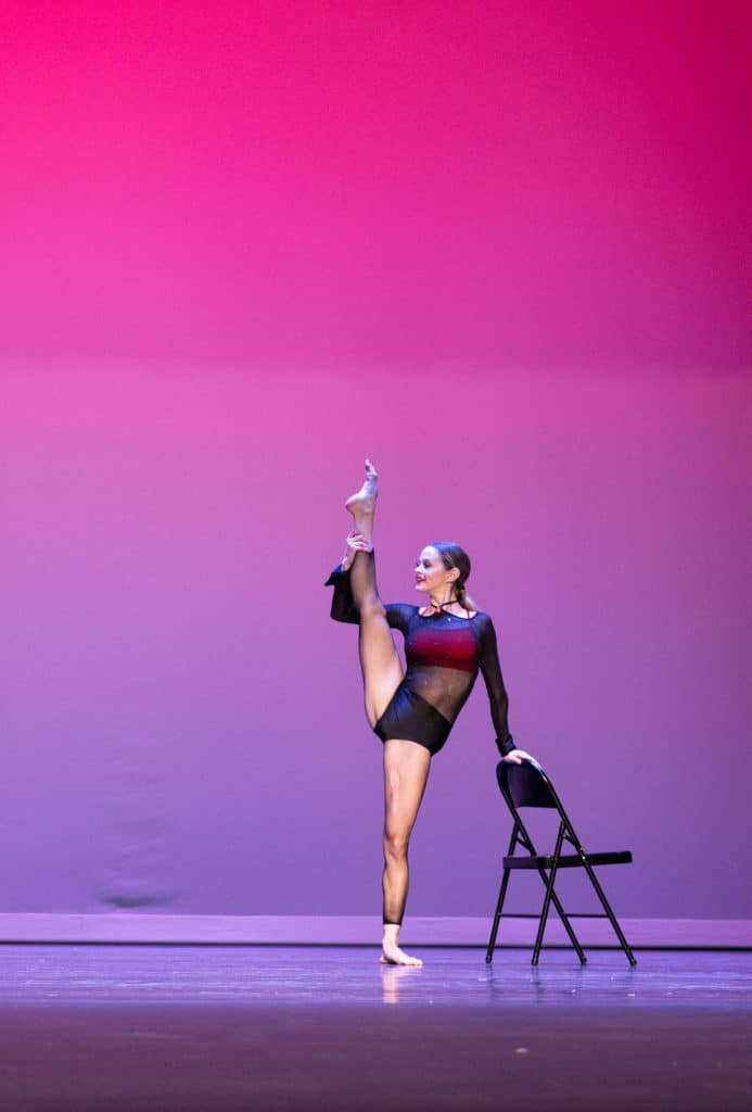 Solo lyrical dancer doing a leg hold onstage.