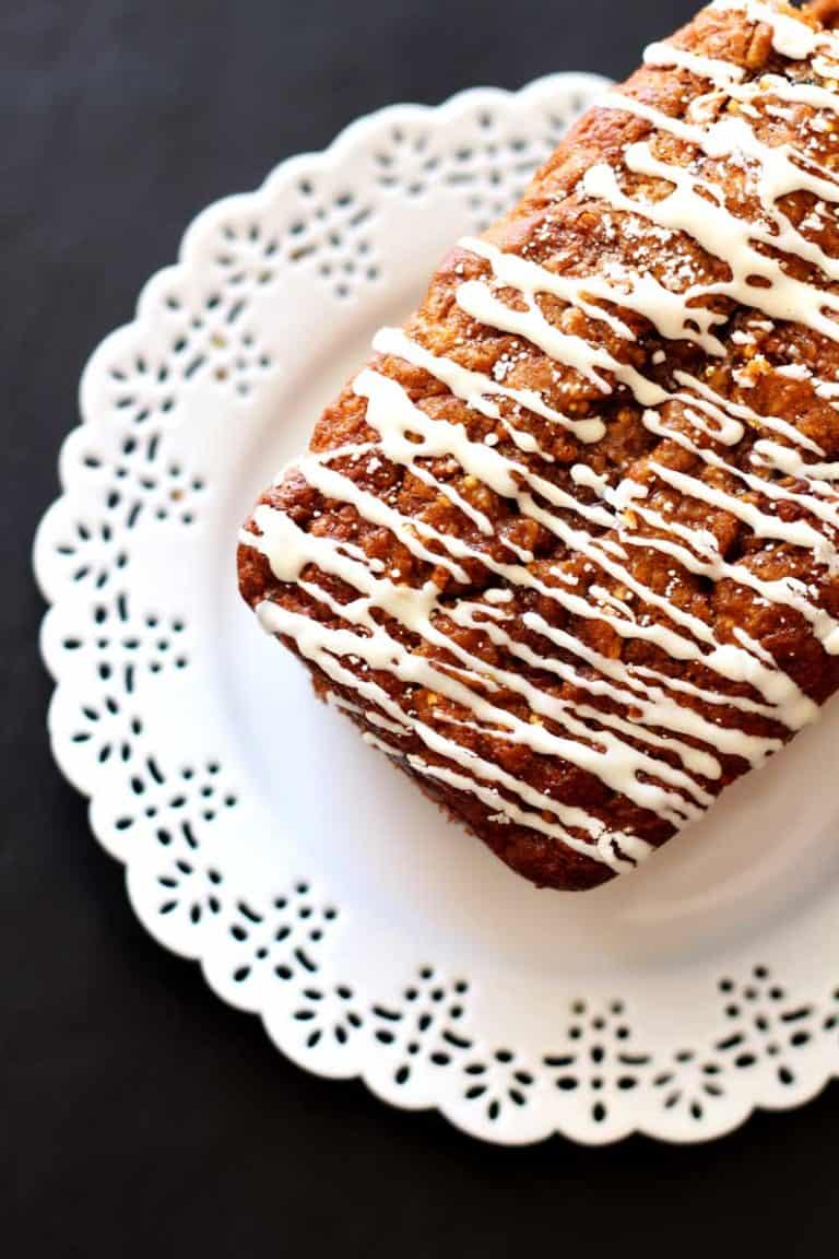 Zucchini Carrot Apple Cake with white frosting sitting on a white plate.